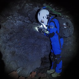 HI-SEAS crewmember exploring Mauna Loa's lava tubes as analogs for lava tubes on Mars and the moon.