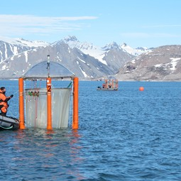 Scientists checking the mesocosms off the coast of Svalbard