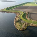 Aerial view of a seawall in the Netherlands protecting farmland that is below sea level.